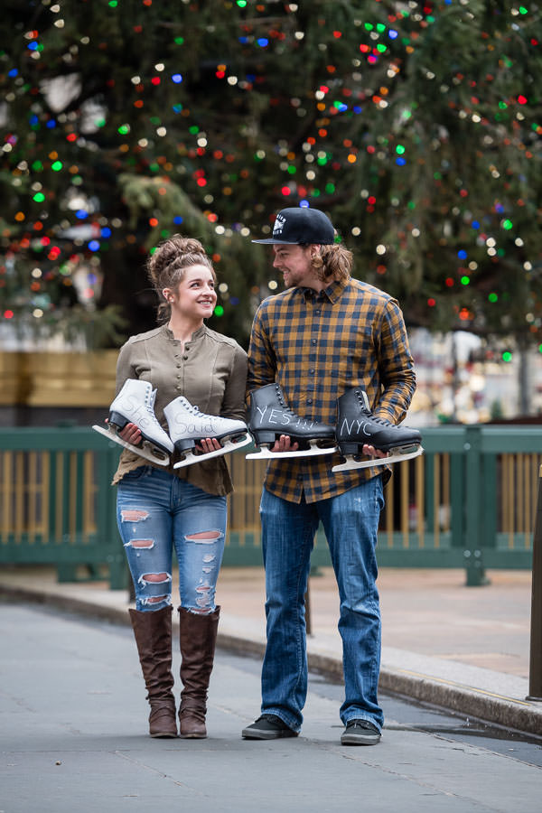 couple holds signed she said yes ice skates for creative proposal photo at rockefeller center