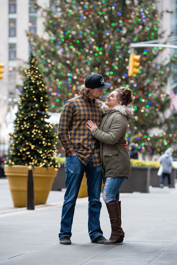 couple hold each other at rockefeller center with christmas tree in the background