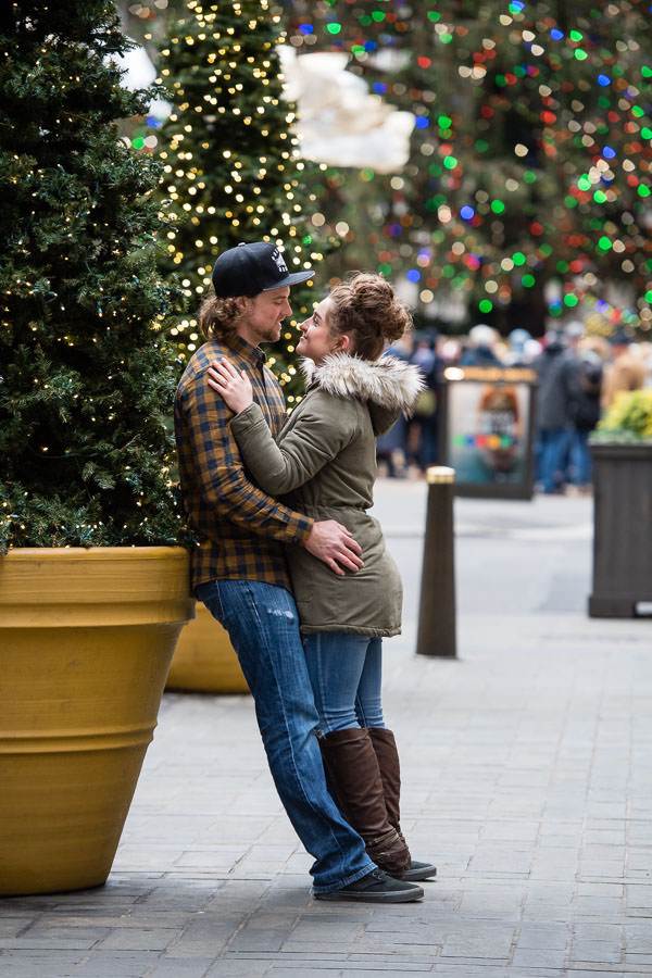 couple holding each other closely in front of rockefeller center christmas tree during their engagement session