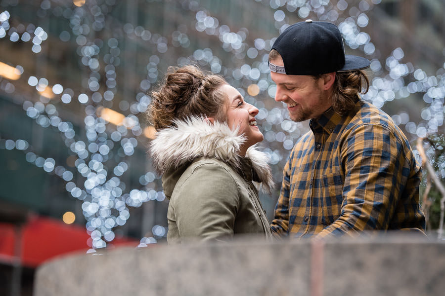 engaged couple smile at each other with white christmas lights behind them during their engagement session at rockefeller center
