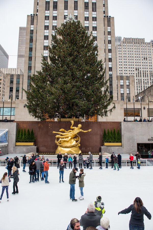 proposal at rockefeller center couple stands in middle of ice skating rink with big christmas tree in the background