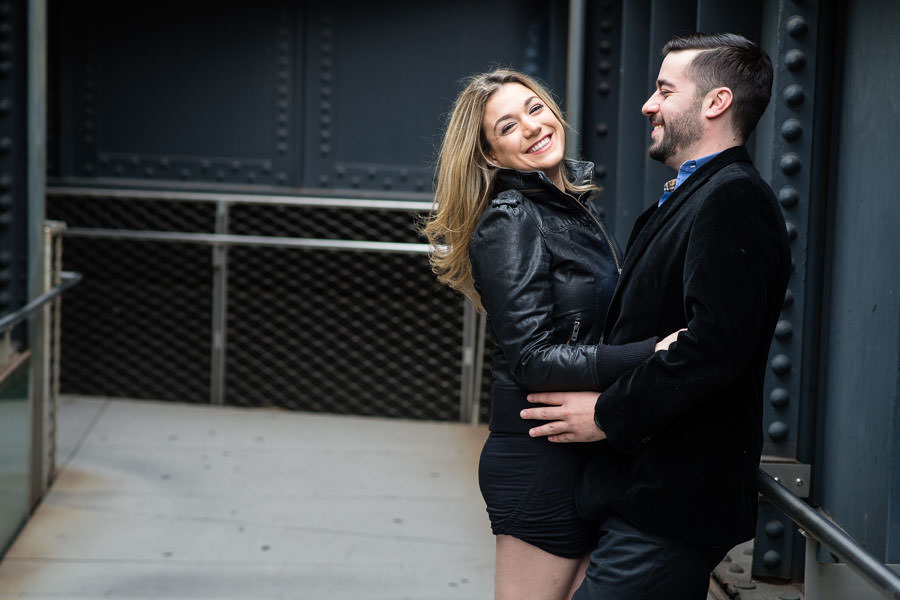 engaged couple holds each other and laughs during their engagement session at highline park