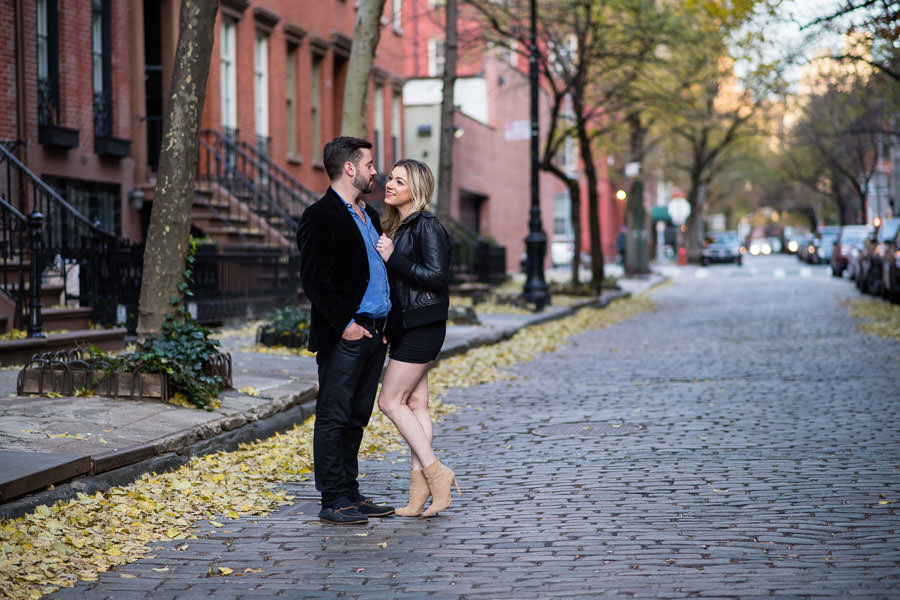 couple standing on cobblestone street with fall foliage in NYC