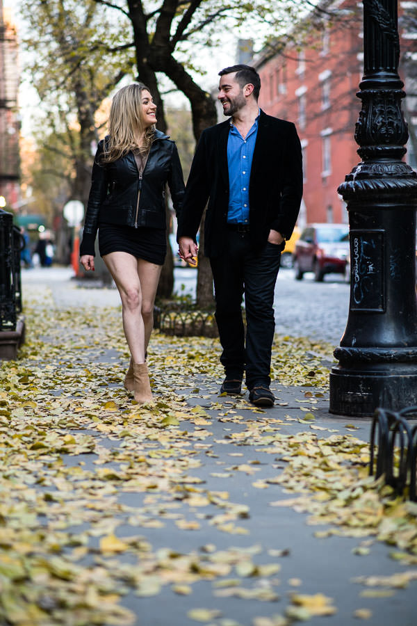 couple walking down sidewalk with fall foliage in NYC during their engagement session