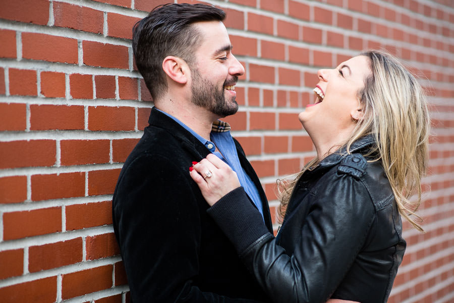 couple laughing in front of red brick wall during their engagement shoot in the meatpacking district