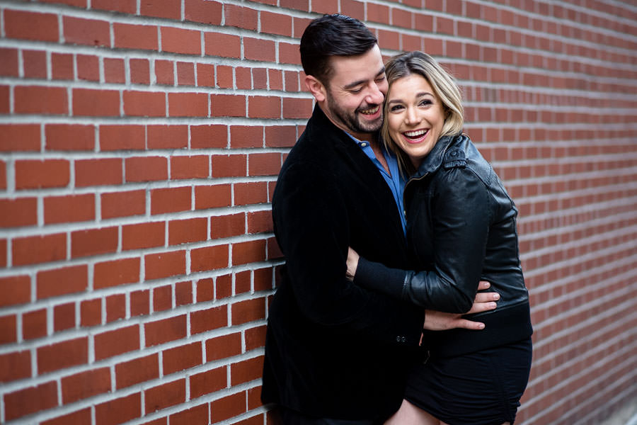 couple holding each other and laughing in front of red brick wall during their engagement session in NYC