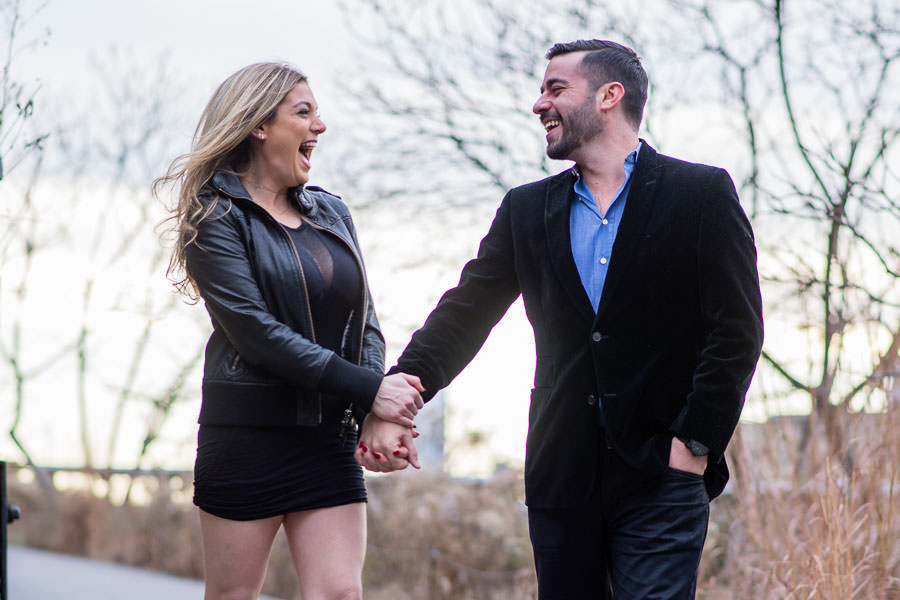 engaged couple hold hands and walk together during their engagement session at highline park