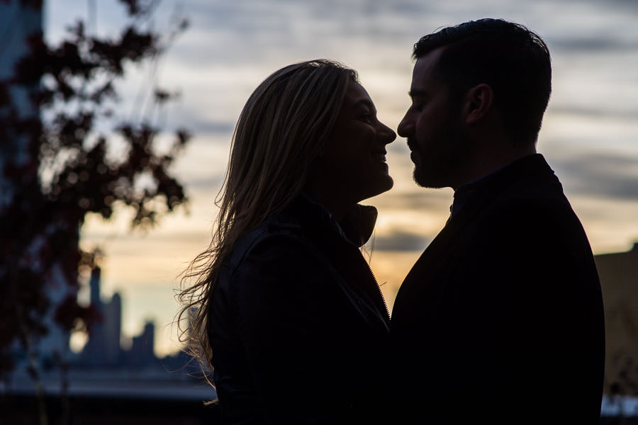 silhouette of couple kissing during sunset at their engagement session in new york city