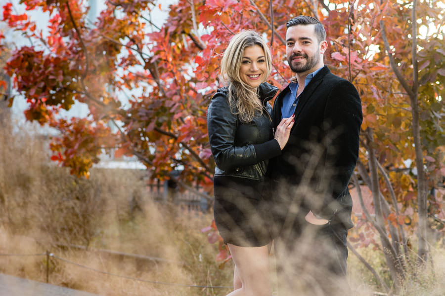 couple poses in front of fall foliage during their engagement session in new york city