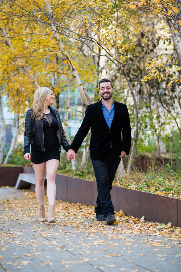 couple holding hands and walking together with fall foliage in NYC