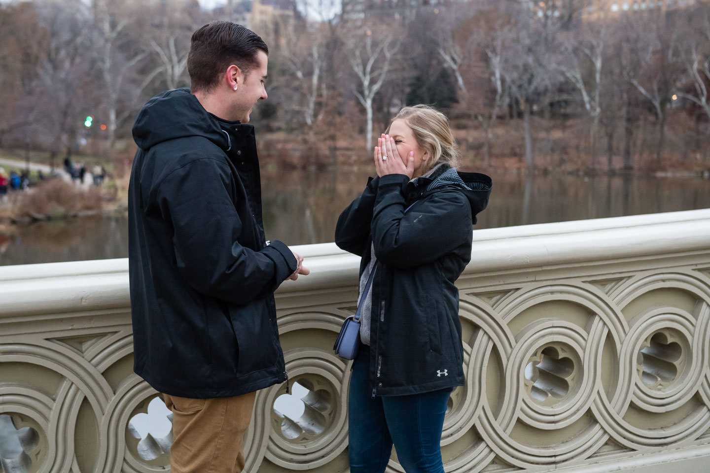 girl covering her face from excitement and emotion after a bow bridge proposal in central park