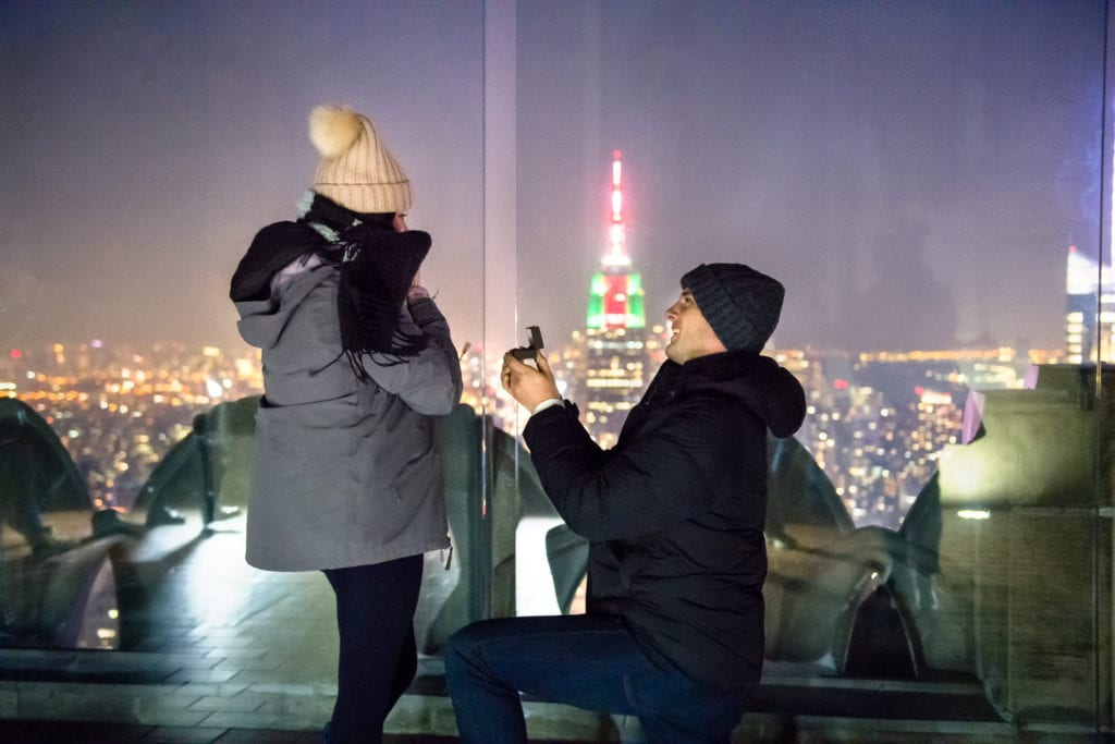 Top of the Rock proposal with empire state building in the background at night in the winter in New York City