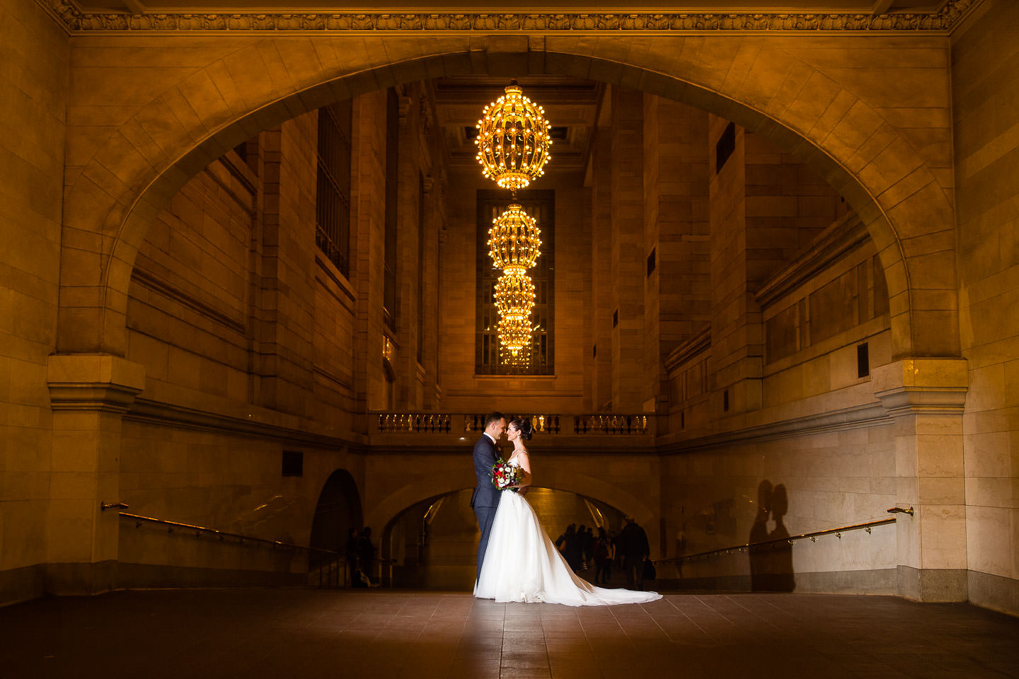 wedding couple holding each other in the middle of grand central station in nyc with chandeliers in the background