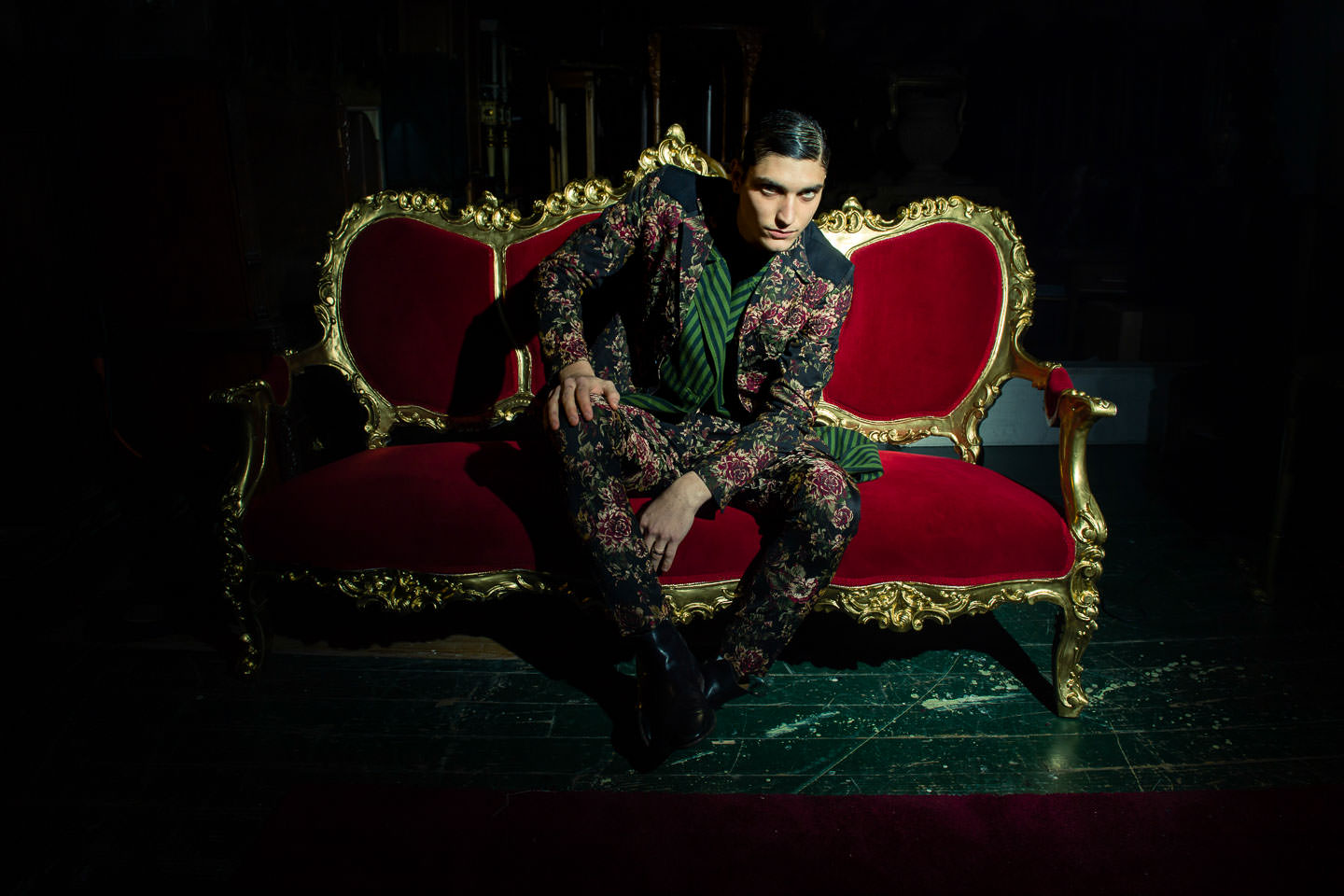 male model in floral suit jacket sitting on red antique couch with golden accents