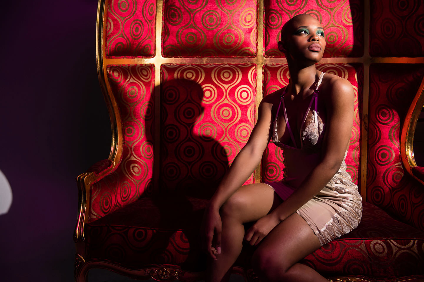 black female model posing on a big red chair in the studio