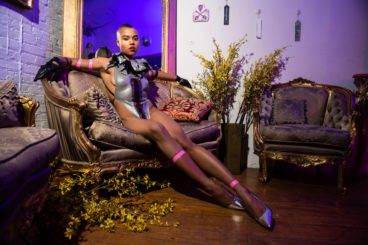 black female model sitting on golden couch with mirror in the background and surrounded by yellow flowers
