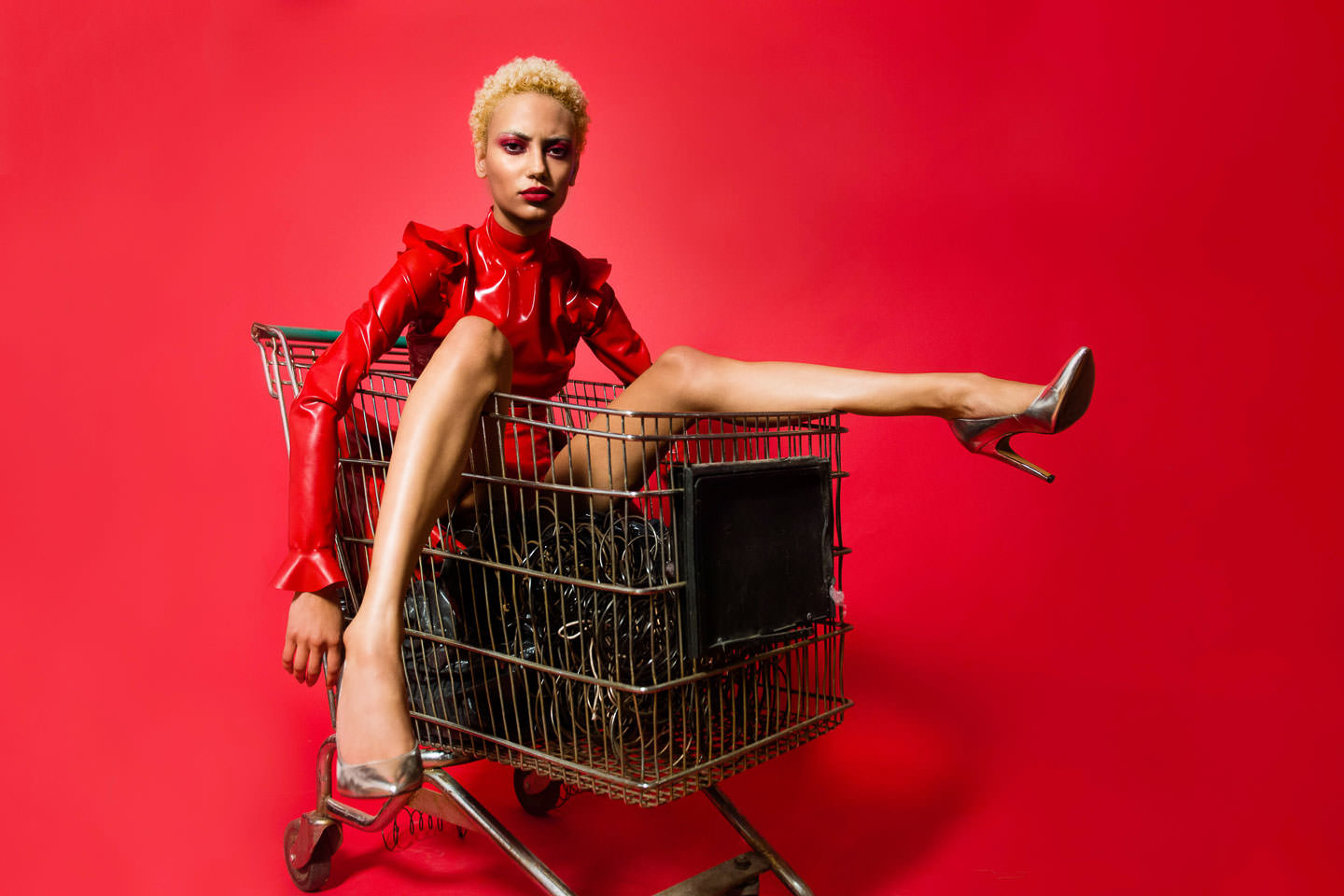 female model wearing red latex suit sits in a shopping cart on red background in studio