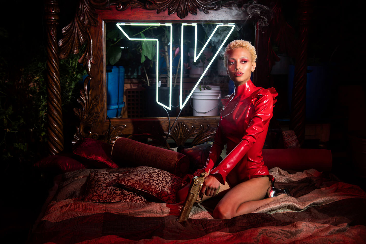 short haired female model wearing red latex suit and holding a golden gun sits on bed after smoking