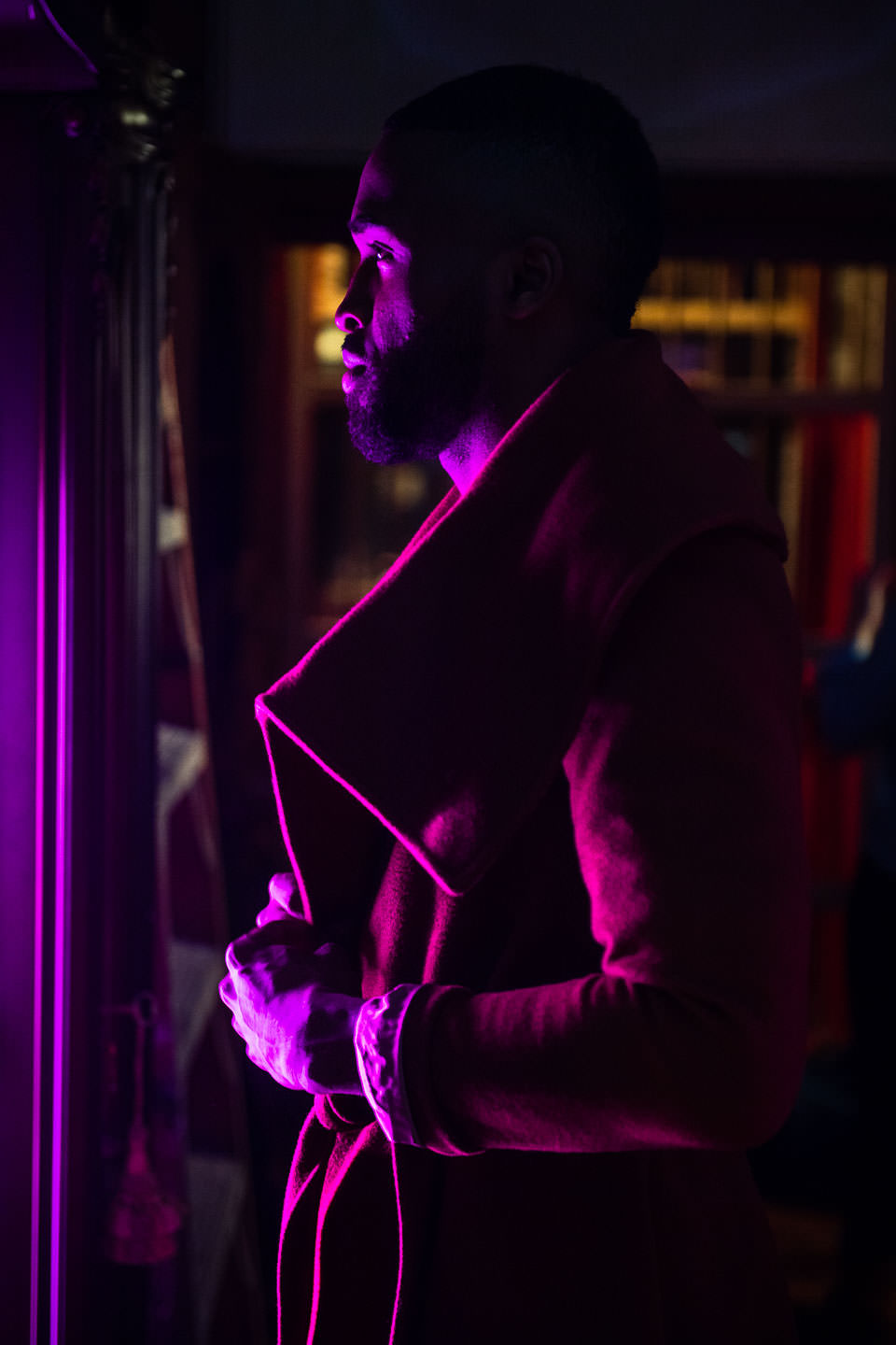 african male model with purple light fixes his jacket