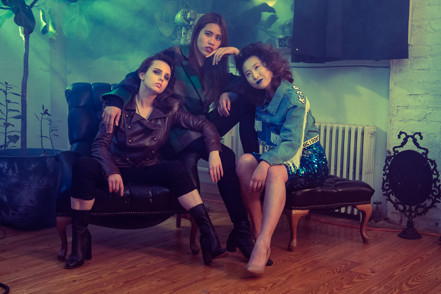 three girl models pose on couch with smoke and a green background