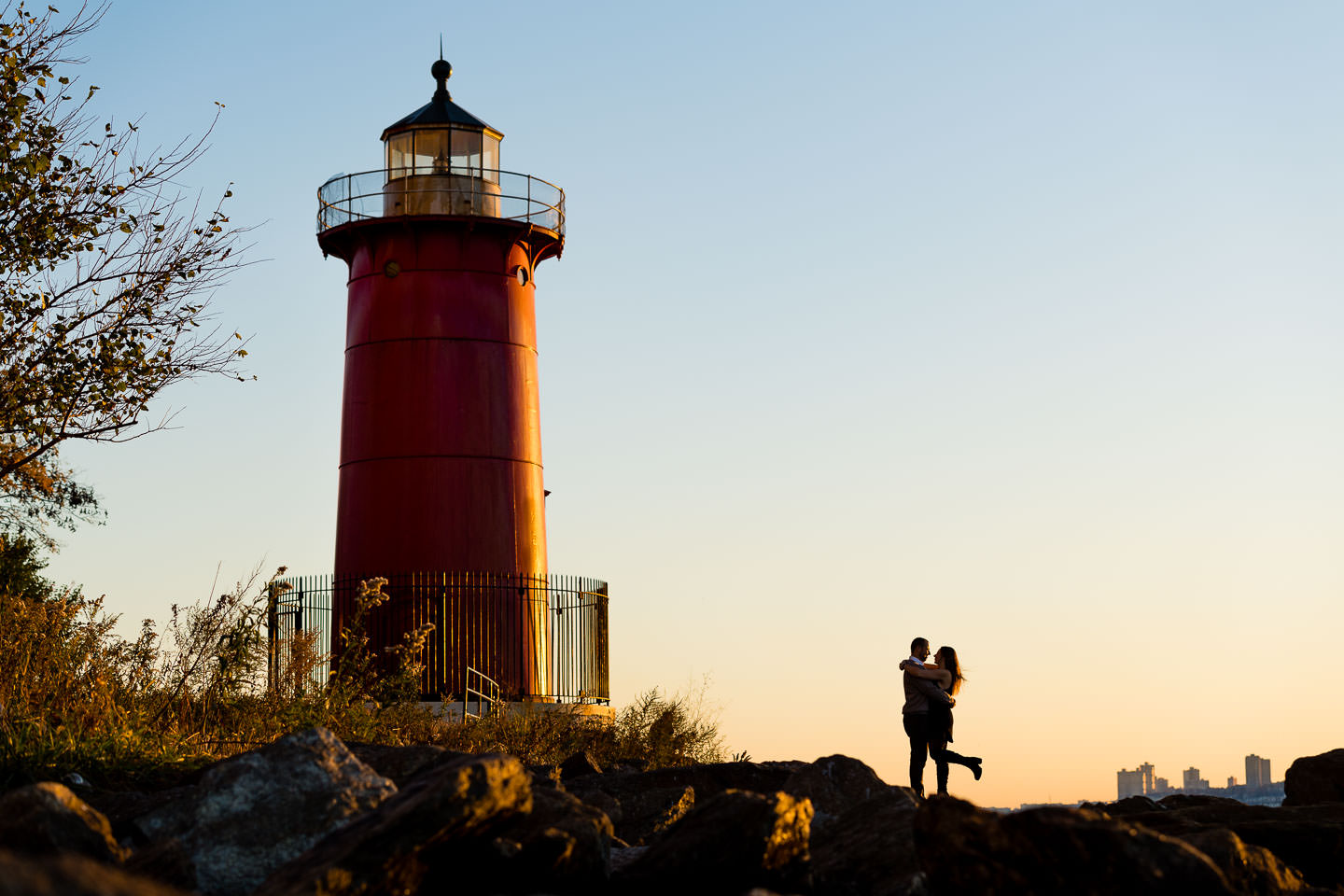 Couple pose at sunset at the little red lightouse in riverside park nyc