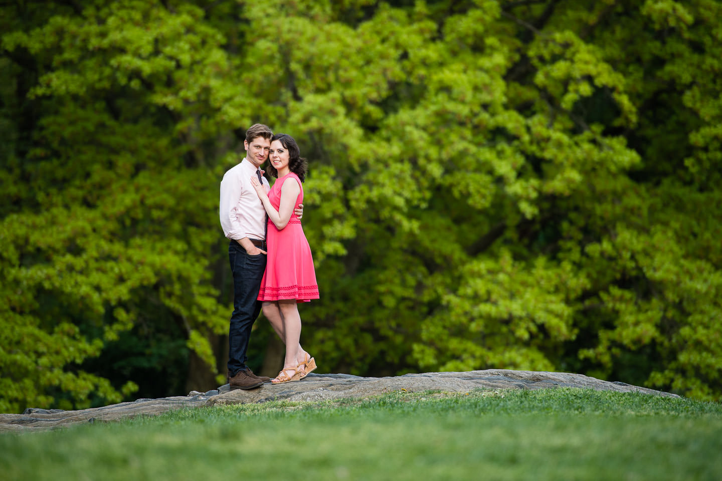 engaged couple guy in slacks and shirt and girl in pink dress stand on rock in central park during engagement session
