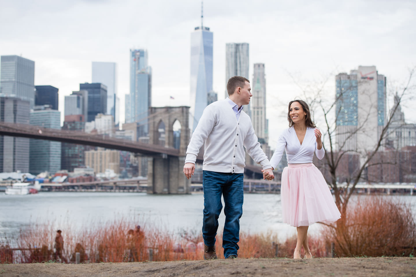 couple holds hands and walks up hill in dumbo brooklyn bridge park with nyc skyline in the background during their engagement sesion