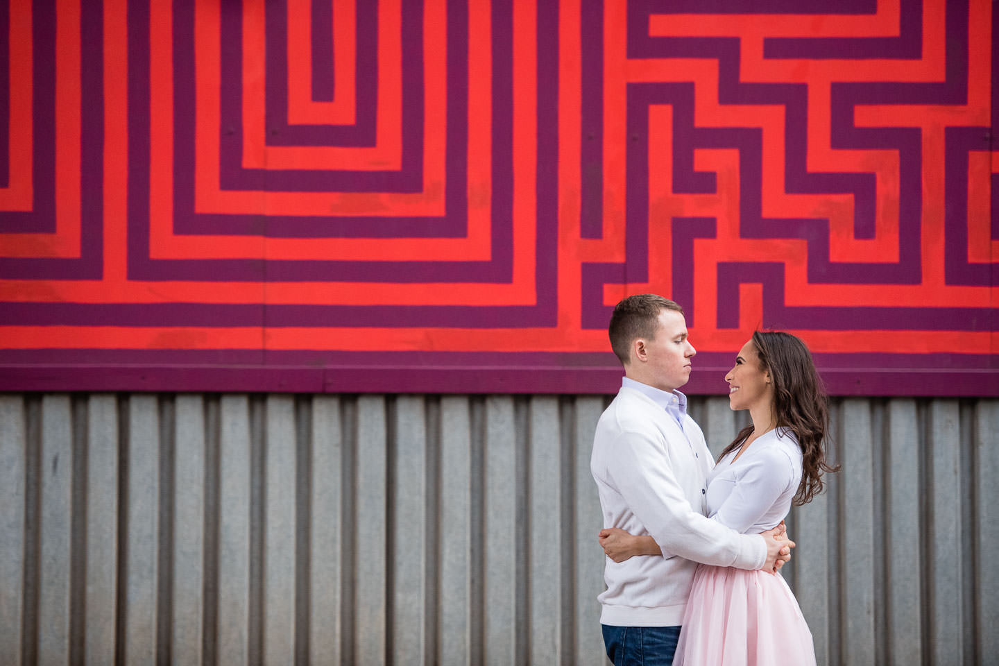 couple poses in front of colorful maze mural in dumbo brooklyn for their engagement session