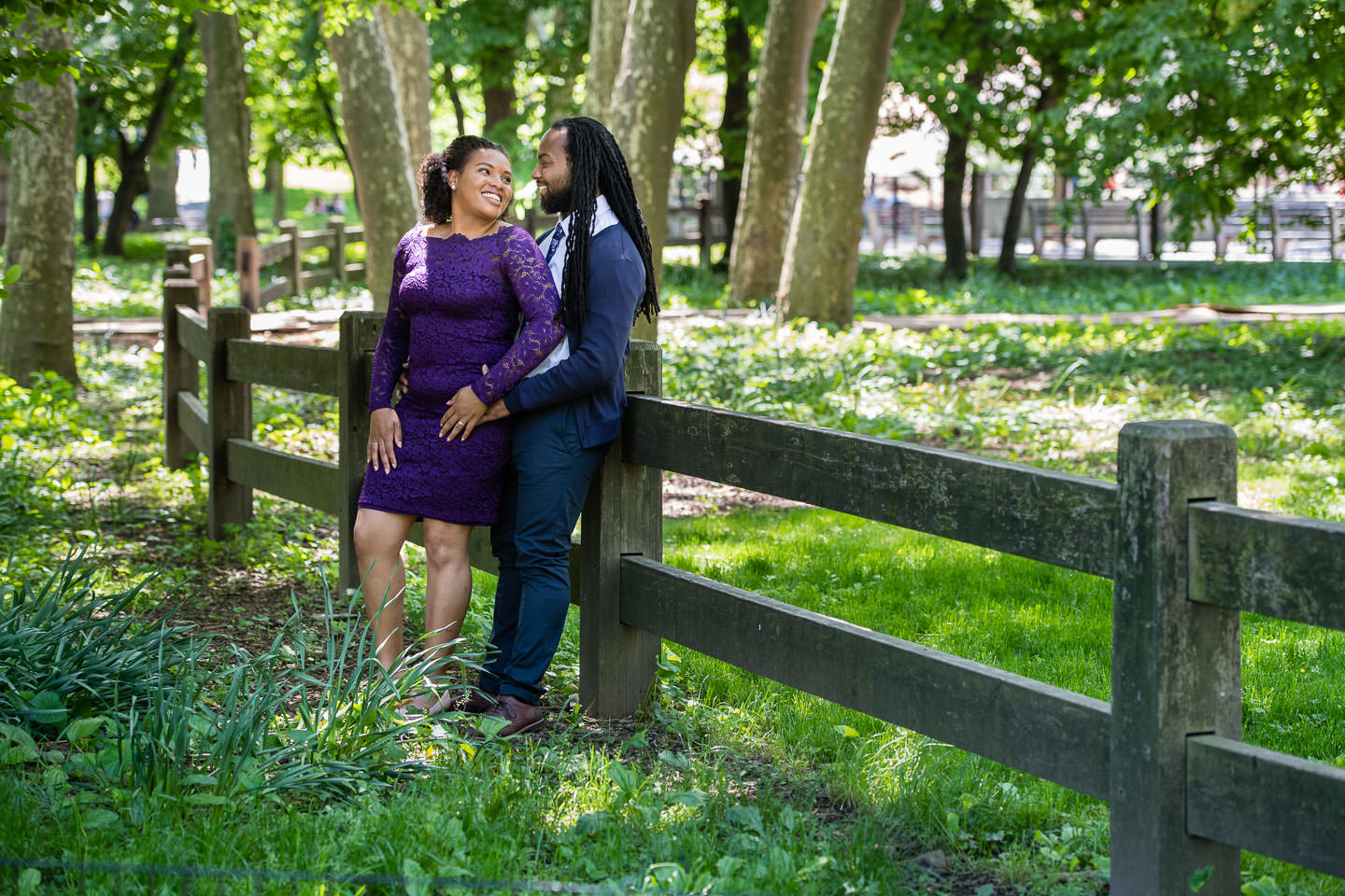 couple poses by fence in central park girl wears purple dress