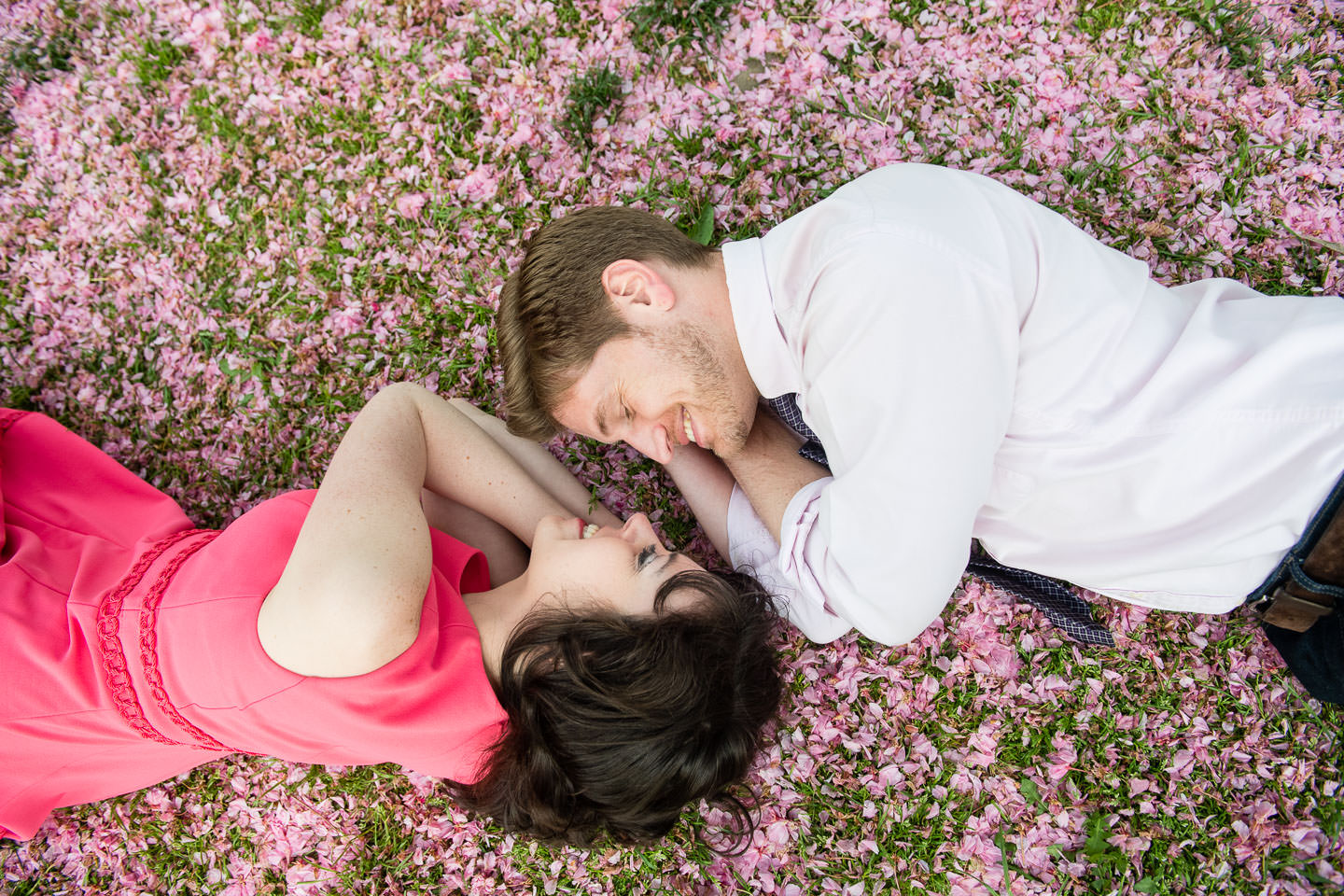 engaged couple laying on bed of flower petals during their spring season engagement session in central park