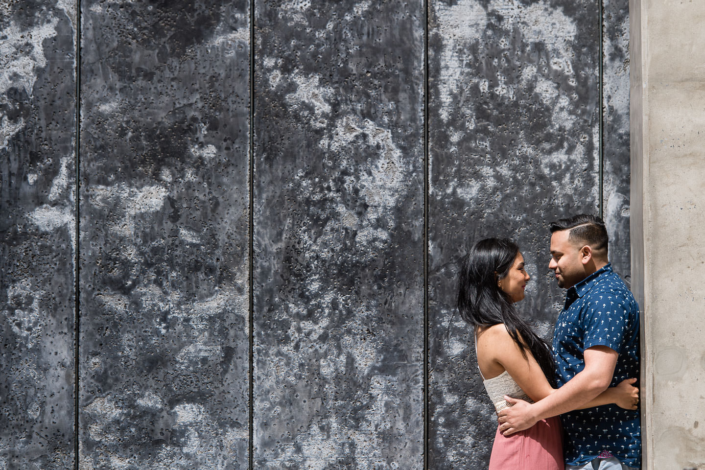 engaged indian couple stand in front of wall in dumbo brooklyn for their engagement session