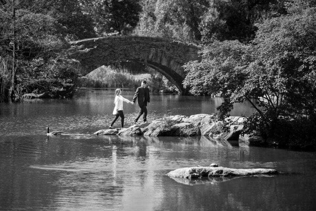 couple holds hands and walks up rock with gapstow bridge in the background in central park nyc