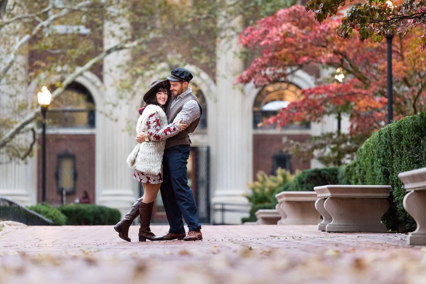 couple poses at columbia university campus in nyc during fall foliage season