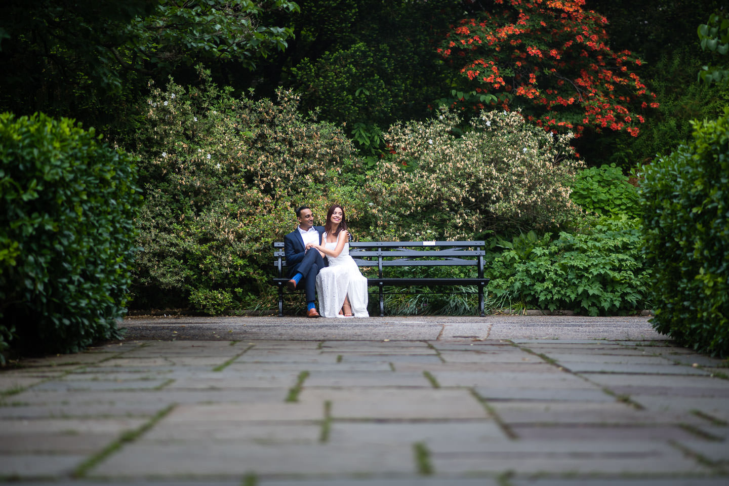 couple sits on bench at their central park conservatory gardens engagement session 2