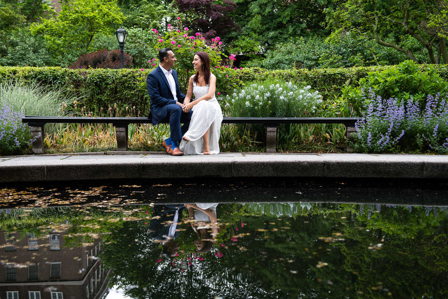 couple sits on bench at their central park conservatory gardens engagement session