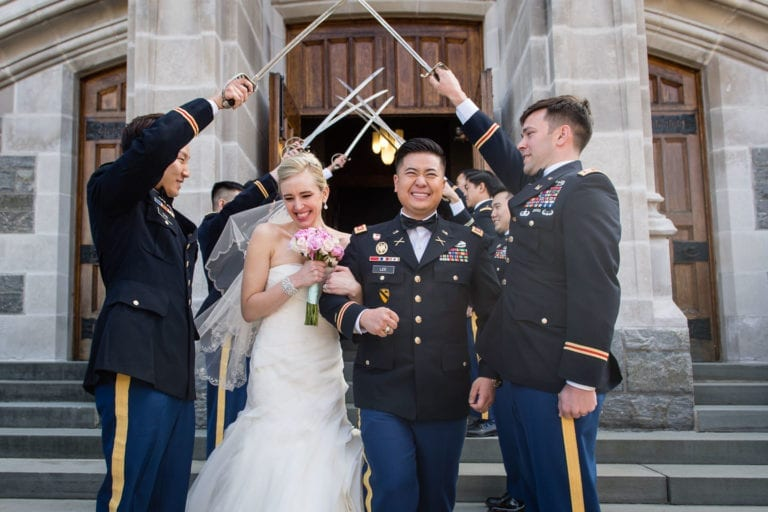 Bride and Groom exit chapel at westpoint military academy in ny under arch of sabers