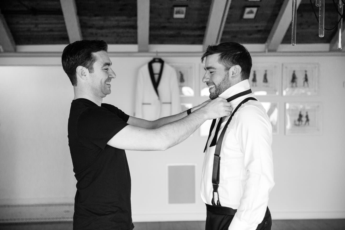 best man helps groom with bowtie with tuxedo jacket hanging in the background
