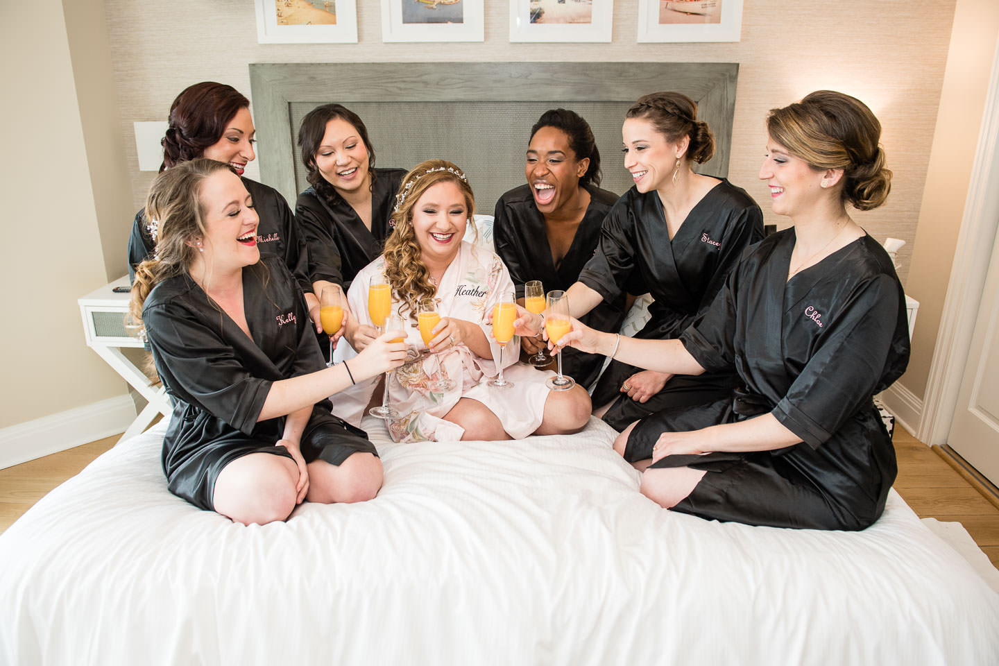bride and bridesmaids sit on bed in bathrobes drinking mimosas during getting ready for wedding at reeds at shelter inn