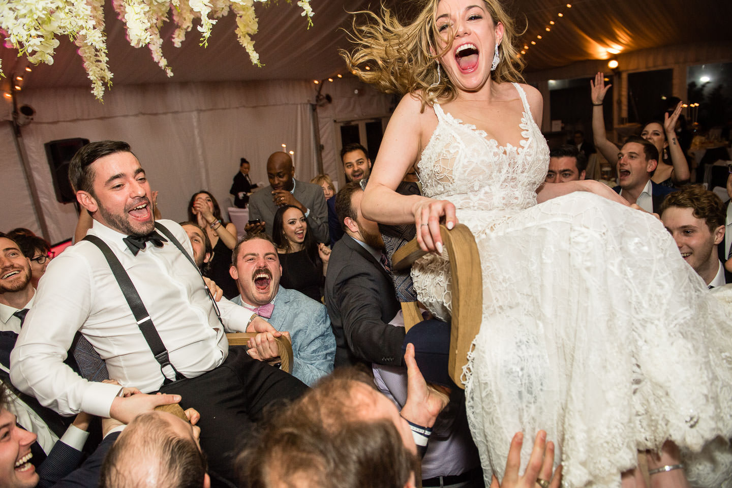 bride and groom are thrown in the air during jewish horah dance at gurneys inn montauk long island wedding