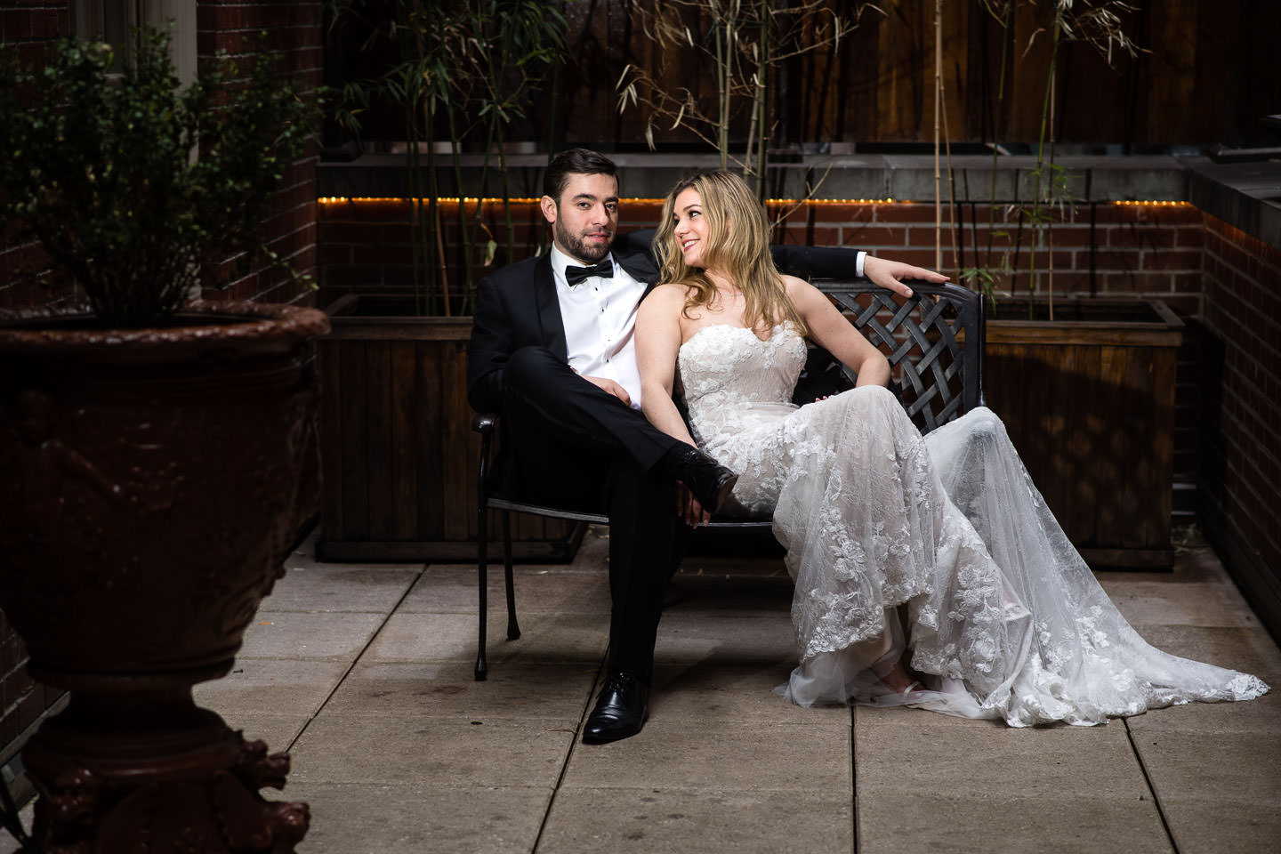 bride and groom sitting on a bench at the lambs club restaurant in nyc