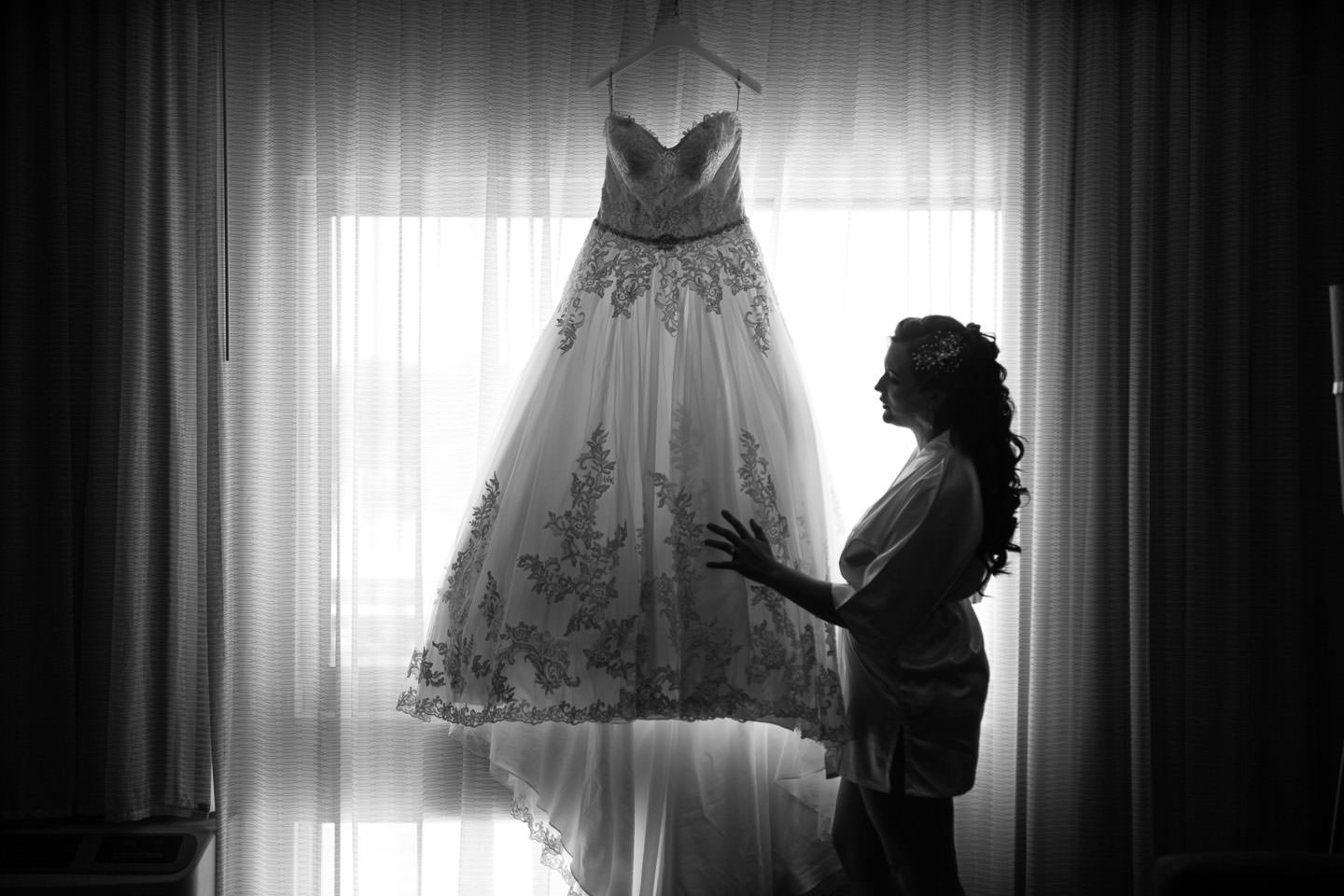 bride with her dress in front of the window
