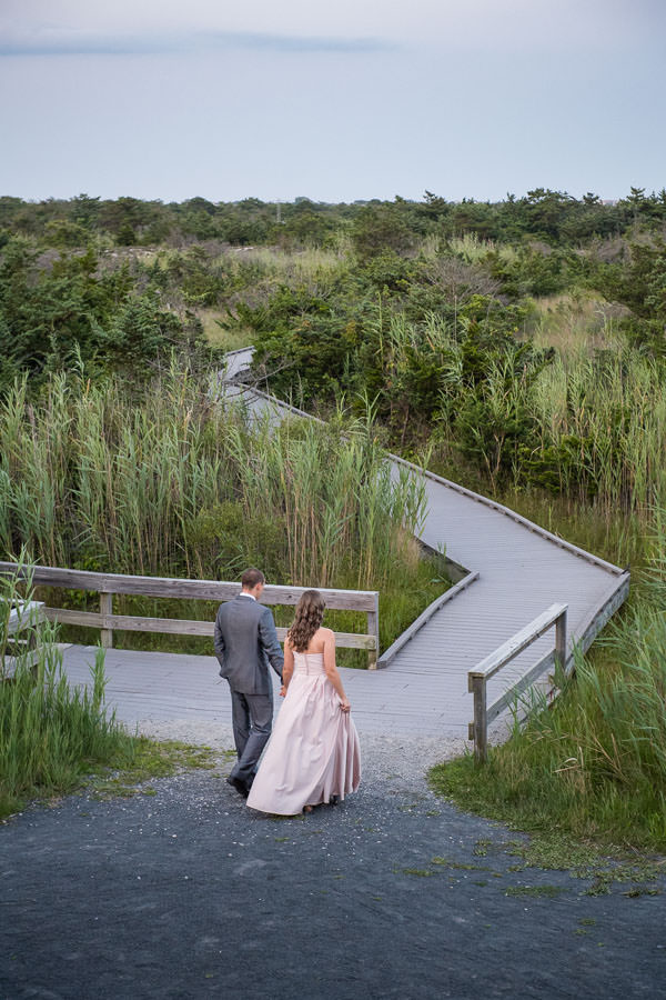couple holding hands and walking along wooden path