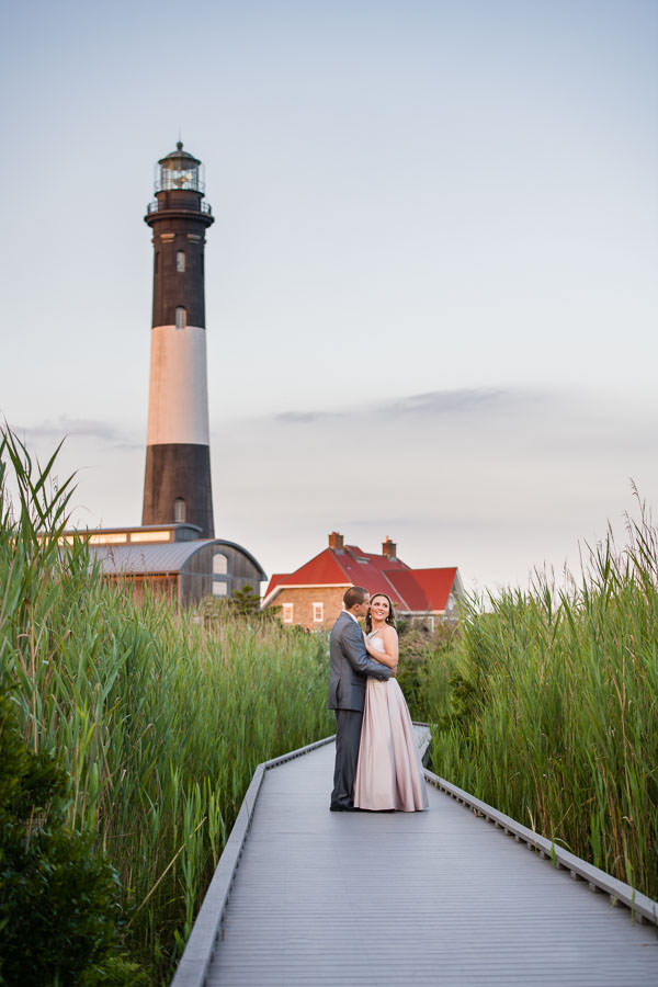 couple holds each other and stands in fron of fire island lighthouse