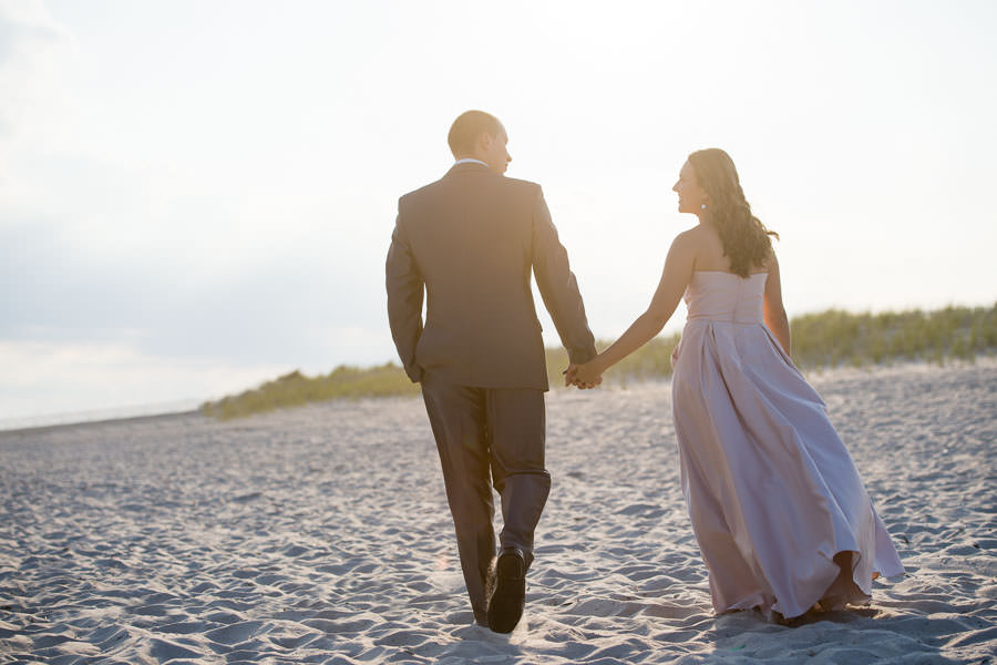 couple holds hands as they walk on the beach in a stunning gown and tuxedo