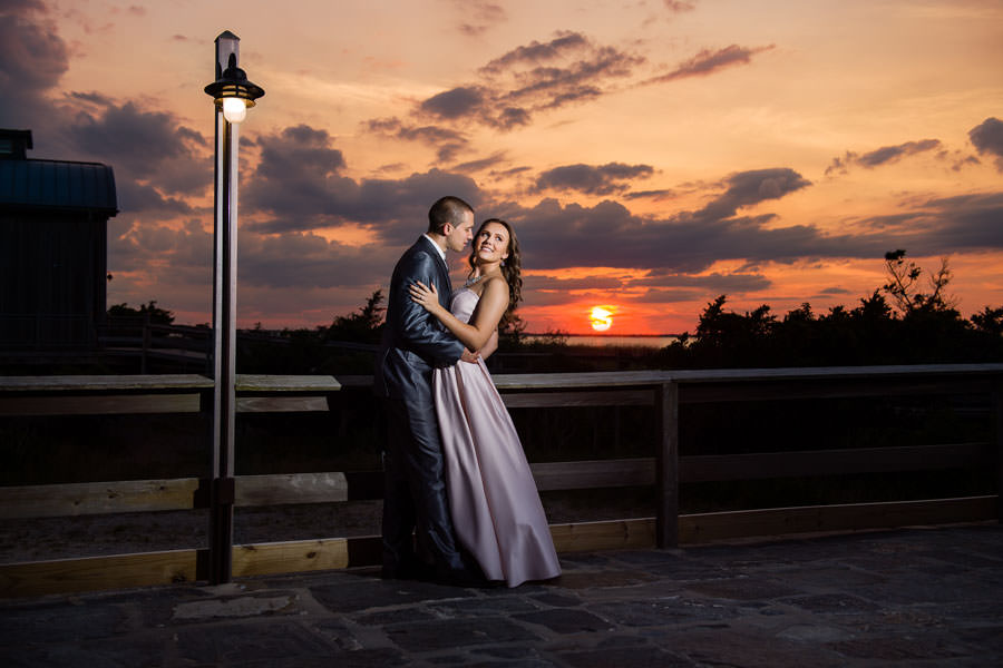 couple poses in front of sunset at fire island