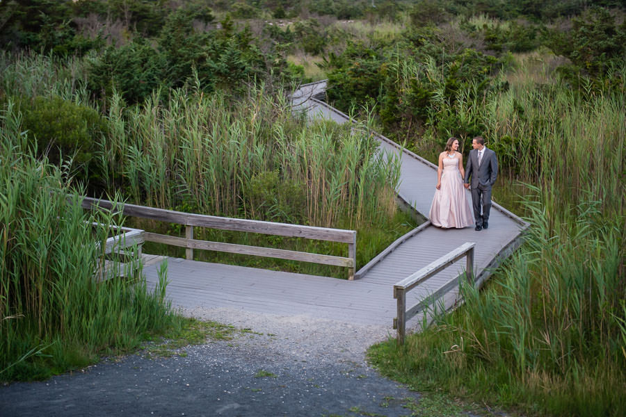 couples walks along path at fire island while holding hands