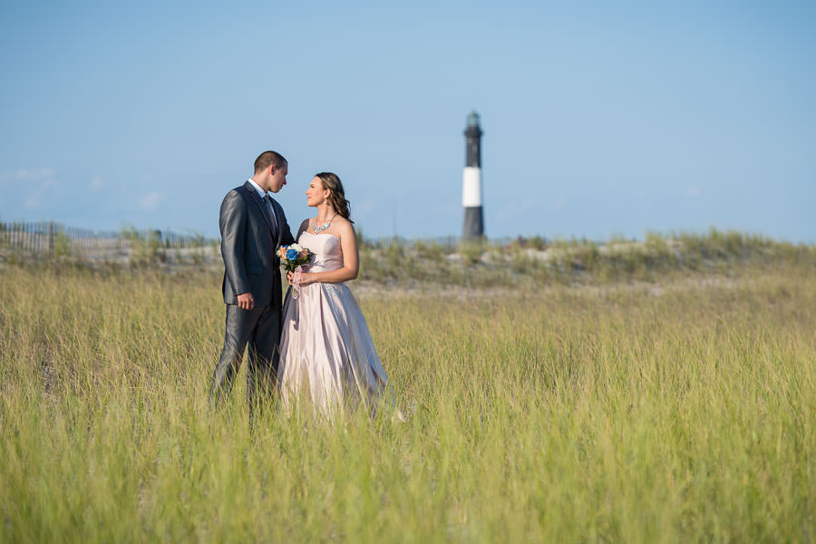 dapper couple in fire island poses on the grass with fire island lighthouse in the background