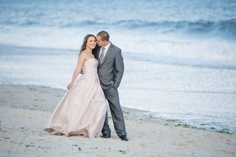 engaged couple in stunning wardrobe poses on the beach in front of the ocean on fire island