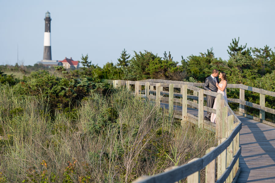engaged couple poses on walking path in fire island leading up to lighthouse
