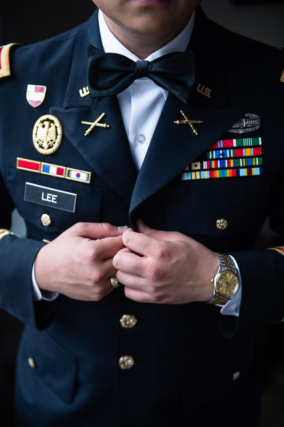 groom buttons his blazer with military badges and ribbons at west point military academy